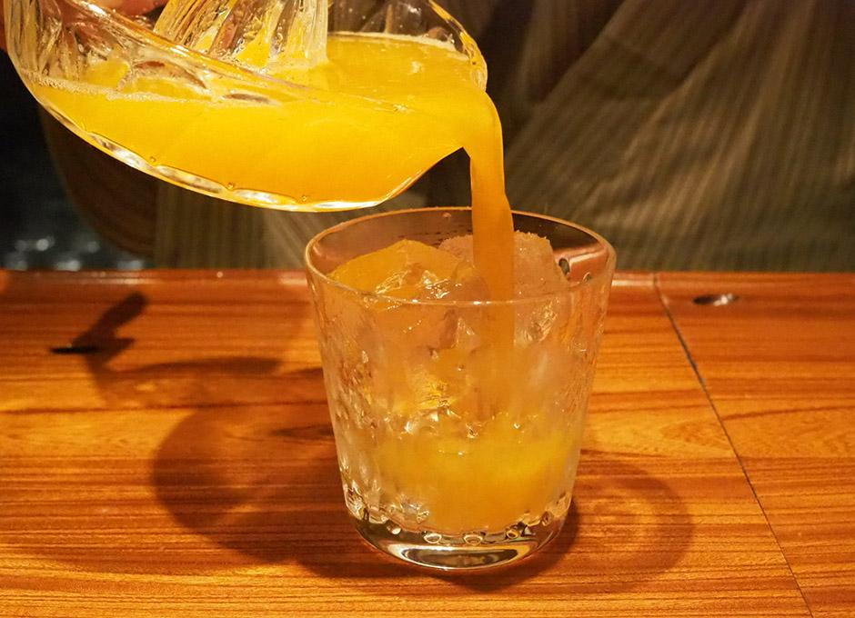 グラスにオレンジジュースを注ぐ
